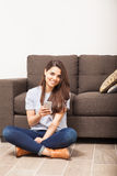 Woman texting on a smartphone at home Stock Photography