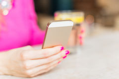 Woman texting on smartphone while sitting in cafe Stock Photos