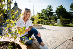 Woman texting on the smartphone sitting in a park Royalty Free Stock Image