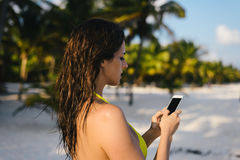 Woman texting on smartphone at tropical caribbean beach Royalty Free Stock Images