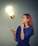 Woman texting using mobile phone looking up at light bulb. Technology idea concept Royalty Free Stock Photo