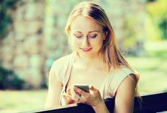 Woman texting using mobile phone in park Stock Images