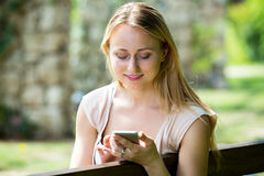 Woman texting using mobile phone in park Royalty Free Stock Image