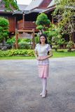 Woman in Thai traditional dress at wooden house stock image