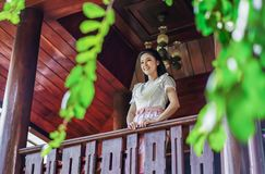 Woman in Thai traditional dress at wooden house royalty free stock photo