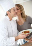 Woman thanking and giving a kiss to cooking chef Royalty Free Stock Photo