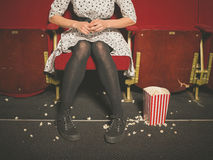 Woman in theater with popcorn on floor Stock Photos