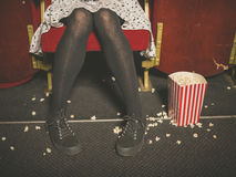 Woman in theater with popcorn on floor Stock Photo