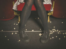 Woman in theater with popcorn on floor Royalty Free Stock Photo