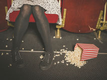 Woman in theater with popcorn on the floor Stock Photos