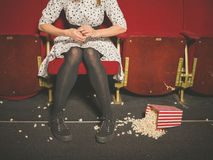 Woman in theater with popcorn on the floor Royalty Free Stock Photo