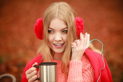 Woman with thermal mug listening music in autumn scenery Royalty Free Stock Photo