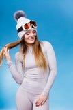 Woman in thermal underwear ski googles. Attractive woman in winter cap gray sports thermal underwear for skiing training ski googles studio shot on blue Stock Photo