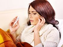 Woman with thermometer having  flue in bed. Royalty Free Stock Photo