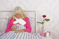 Woman with thermometer sitting in bed Royalty Free Stock Photos