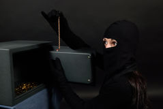 Woman thief breaks into a safe and pulls out a gold chain. She opened the safe and found a gold chain Stock Image