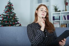 Woman think about christmas wih list on sofa Royalty Free Stock Photos