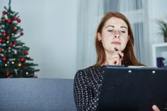 Woman think about christmas wih list on sofa Stock Photos