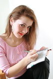 Woman thinking. Young woman is writing something and thinking (See also my other pics royalty free stock photo