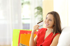 Woman thinking with credit card Stock Photos