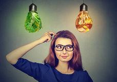 Woman thinking deciding on diet looking up at junk food vegetables light bulbs Stock Photos