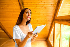 Woman thinking with digital tablet in the wooden Stock Photography