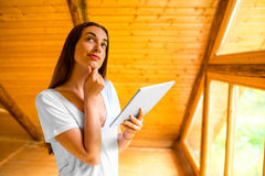 Woman thinking with digital tablet in the wooden Royalty Free Stock Images