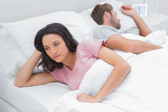 Woman thinking in her bed next to her sleeping husband Stock Image