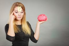 Woman thinking and holding fake brain Royalty Free Stock Photography