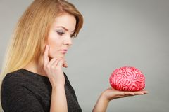 Woman thinking and holding fake brain stock images