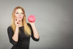 Woman thinking and holding fake brain royalty free stock photo