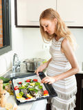 Woman is thinking how to cook fish. Long-haired pregnant blond is thinking how to cook fish in fryingpan at kitchen Royalty Free Stock Photo