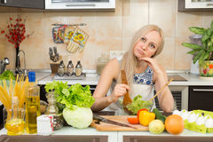 Woman thinking at the kitchen table Stock Photo