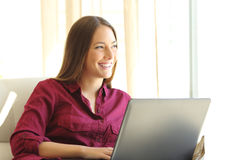Woman thinking with a laptop at home Royalty Free Stock Photo