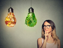 Woman thinking looking up at junk food and green vegetables shaped as light bulb Royalty Free Stock Photo