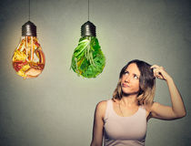 Woman thinking looking up at junk food and green vegetables shaped as light bulb Royalty Free Stock Image