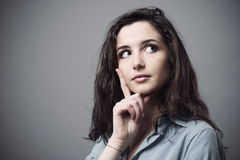 Woman thinking and making plans. Beautiful young woman thinking with hand on chin Royalty Free Stock Photos