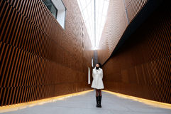 Woman thinking about modern architecture. A woman wearing a white coat looking up Stock Photo