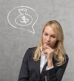 Woman thinking about money. Businesswoman thinking and drawing money bag on wall Royalty Free Stock Photos