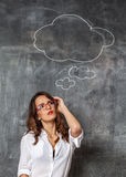 Woman thinking near blackboard with empty mind cloud Stock Photos