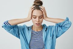 Woman thinking nervously problems home, feeling concerned fed up problematic holding hands on head looking down, trying. Take control over emotions, get stock images