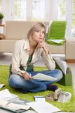 Woman thinking with paper in hand Royalty Free Stock Images