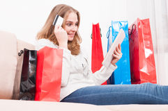 Woman thinking and shopping online holding card with bags around. Pretty woman thinking and shopping online holding credit or debit card with bags around like Royalty Free Stock Photo