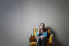 Woman thinking. Woman sitting on a chair thinking royalty free stock photo