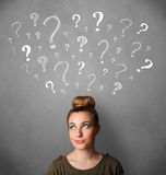 Woman thinking with sketched question marks all over her head. Pretty young woman thinking with sketched question marks all over her head stock photos
