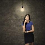 Woman thinking under light bulb Royalty Free Stock Image