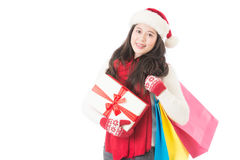 Woman thinking wearing santa hat and holding gifts Stock Image