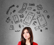 Woman thinking about what phone to buy. Happy young woman looking up, thinking what mobile phone to buy stock images