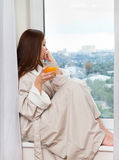 Woman thinking at the window. Woman thinking and drinking juice at the window Royalty Free Stock Photo