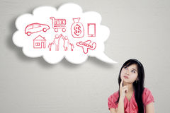 Woman thinks her dreams on cloud speech. Young businesswoman thinks her dream while looking at cloud speech royalty free stock image